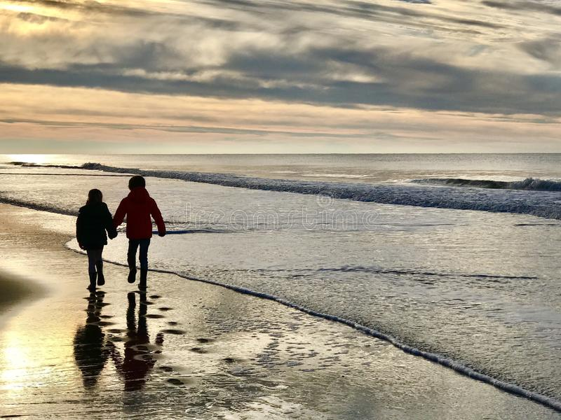 Walking together. Brother and sister walking along the shores royalty free stock photos