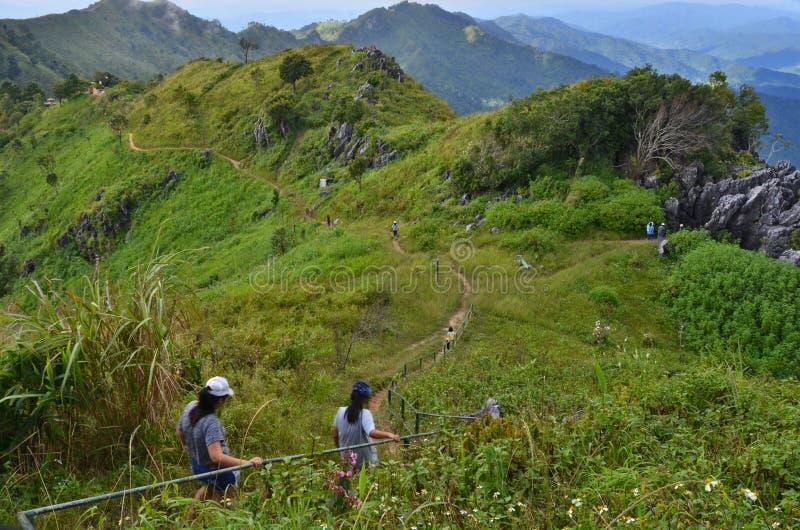 Walking tourist down to the ridge of mountain stock photos