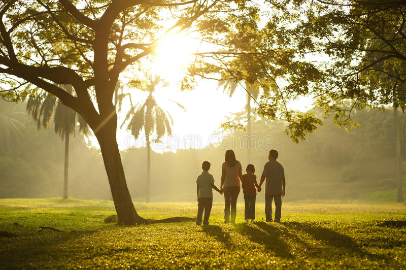 Walking towards the light. Asian family holding hands and walking towards light