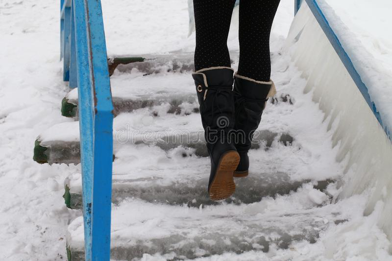 Walking up in a boots on an ice-bound stairs. Walking up in a boots an ice bound stairs in the beach in winter stock image