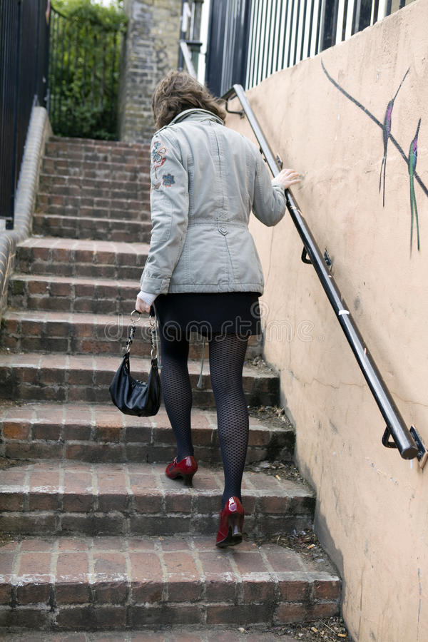 Walking up stairs to higher level. Red shoes. Urban style stock photo