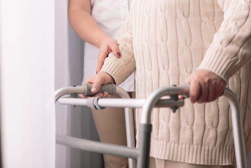 Walking with walker. Close-up of older women walking with walker stock image