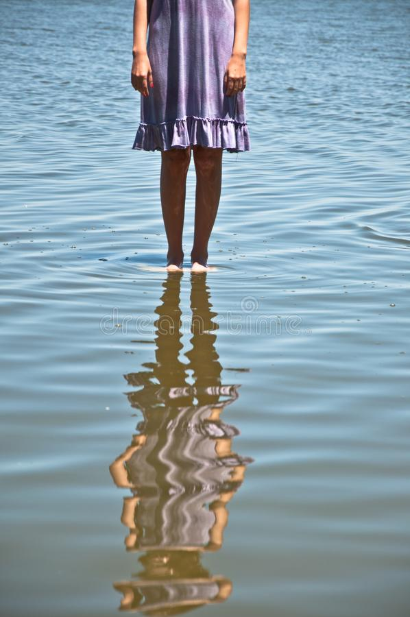 Walking on the water. We can see a girl standing up on the water of the lake royalty free stock photo