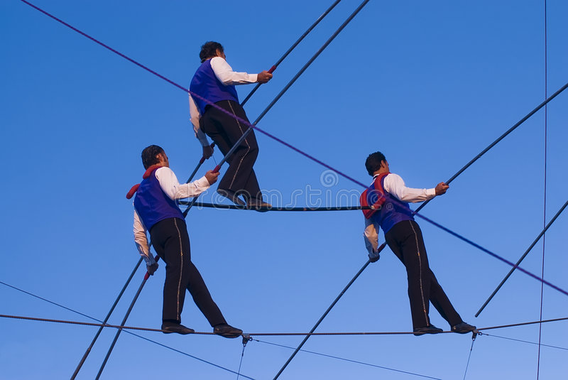 Walking the Wire. Three tight rope walkers on a high wire royalty free stock photos