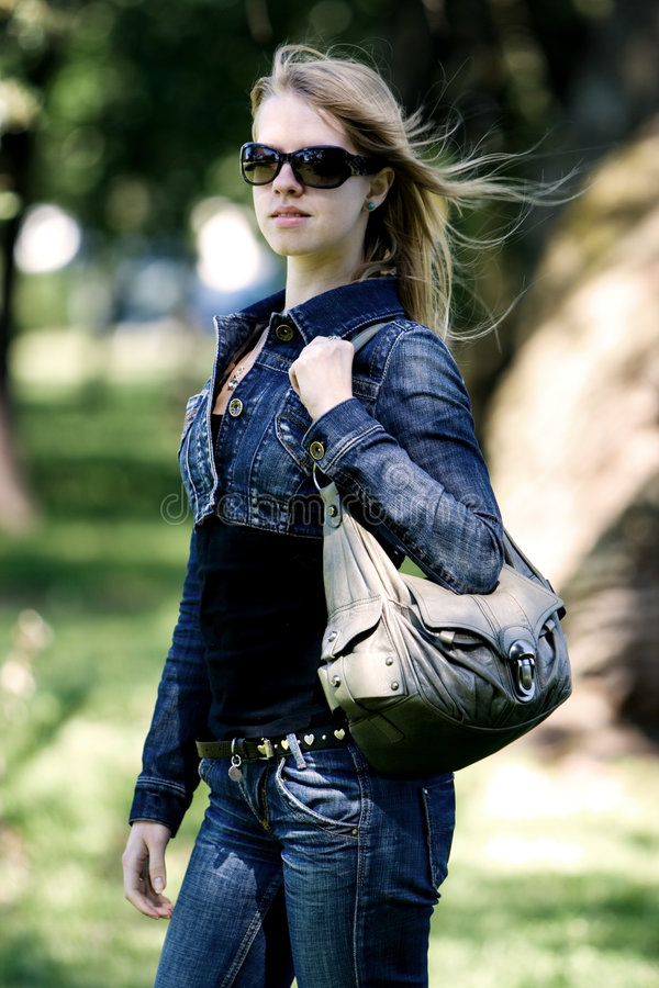 Walking woman in black sunglasses royalty free stock images