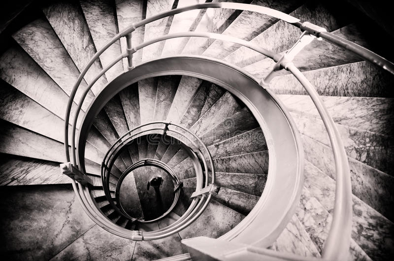 Walking woman in center of spiral stairs royalty free stock photos