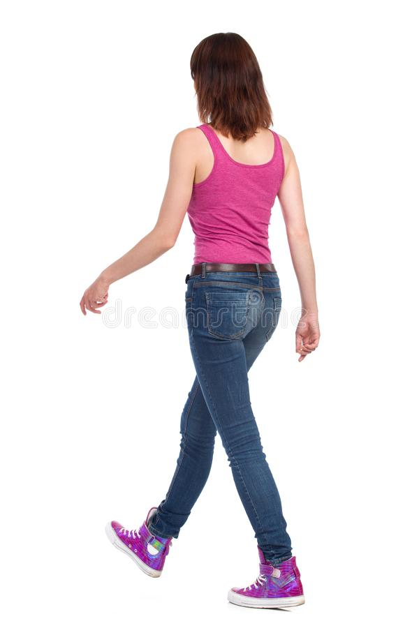 Walking Woman In Pink Tank Top. Jeans And Sneakers. Rear Side View. Young woman in jeans, pink tank top and sneakers is walking. Rear side view. Full length royalty free stock photo
