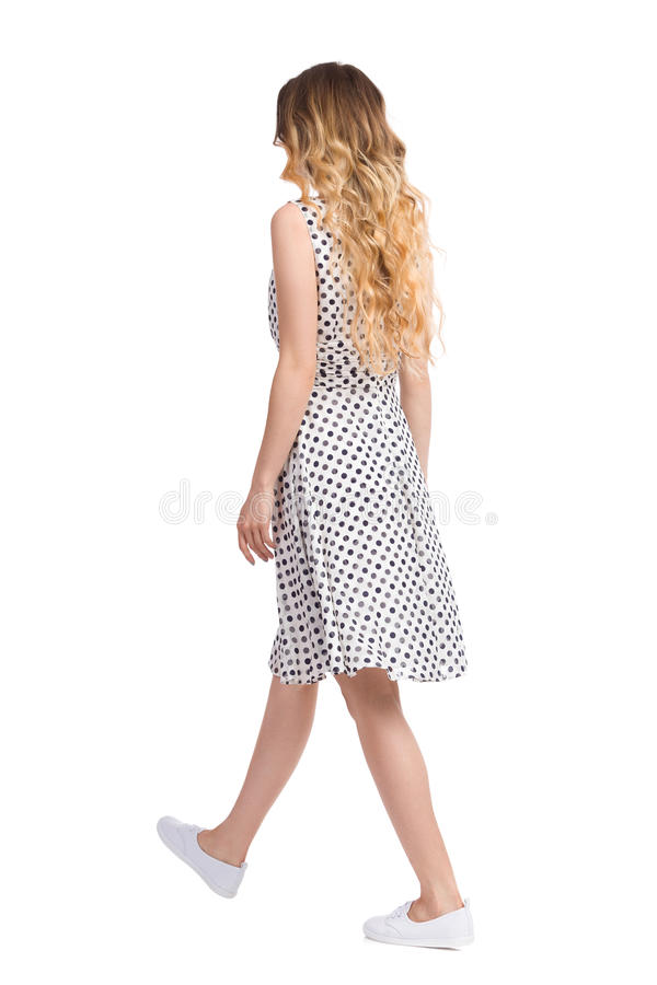 Walking Woman In White Summer Dress And Sneakers Rear View stock photography