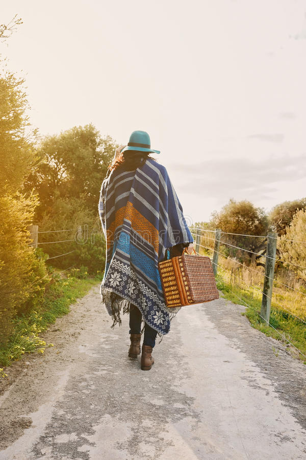 Walking young hipster girl in poncho with vintage suitcase stock photos