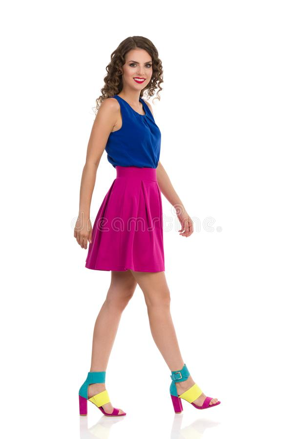 Walking Young Woman In Colorful High Heels, Pink Mini Skirt And Blue Top. Beautiful young woman in colorful high heels, pink mini skirt and blue top is walking stock photography