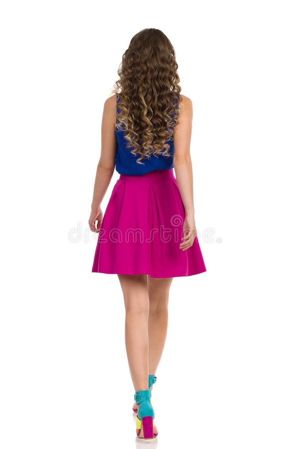 Walking Young Woman In Colorful High Heels, Pink Mini Skirt And Blue Top, Rear View. Beautiful young woman in colorful high heels, pink mini skirt and blue top royalty free stock photography