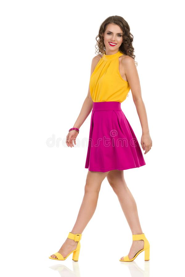 Walking Young Woman In Yellow High Heels And Pink Mini Skirt. Beautiful young woman in yellow high heels and pink mini skirt is walking, looking at camera and royalty free stock images