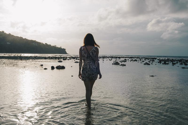 Walks through the shallow waters. The girl walks through the shallow waters of the sea at low tide at sunset. In the water, stones can be seen. In the background stock photography
