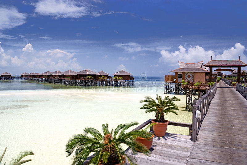 Walkway and Chalets on Stilts. Image of a walkway and chalets on stilts on a remote Malaysian tropical island with deep blue skies and crystal clear waters stock photo