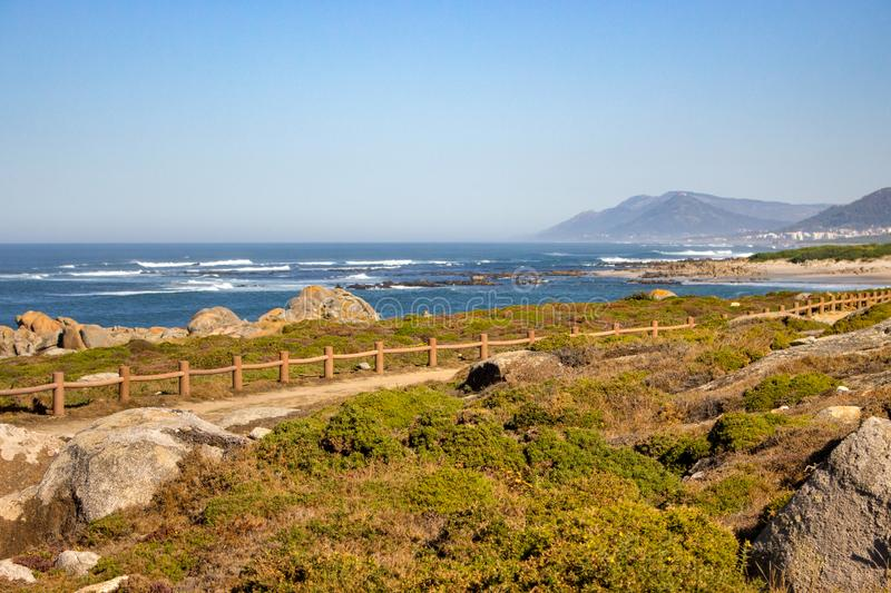 Walkway with fence along Atlantic Ocean coast with mountain on background. Portugal nature. Moss and grass on rocks at seaside. stock images