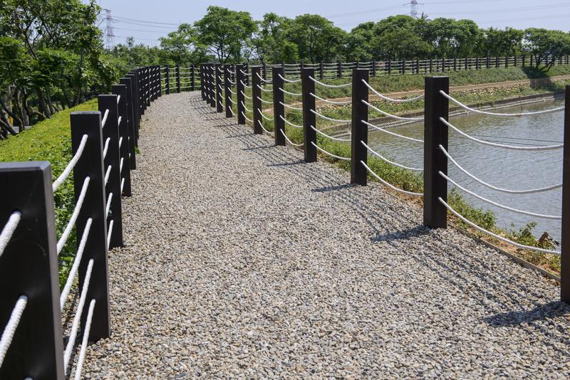 An pebble walkway fenced with rope along the pond royalty free stock image