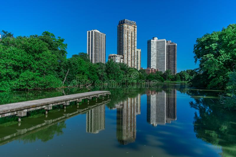 Side View of North Pond in Chicago with Building Reflections. The walkway at North Pond extending out towards the water with residential building reflections royalty free stock photo