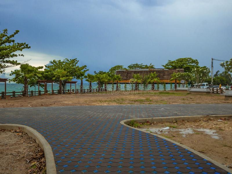 Walkway in the Park near the ocean under cloudy sky. Summer concept royalty free stock images