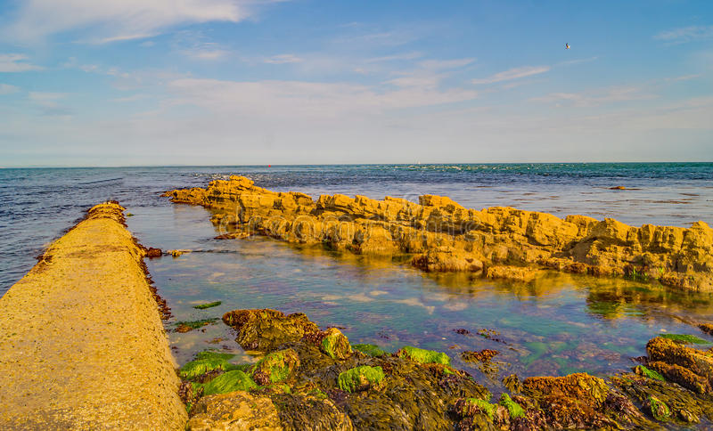 At Swanage Dorset a narrow path stretches out to a blue horizon, an empty walkway into the sea. A narrow walkway at Swanage Peveril Point partly submerged by stock photo