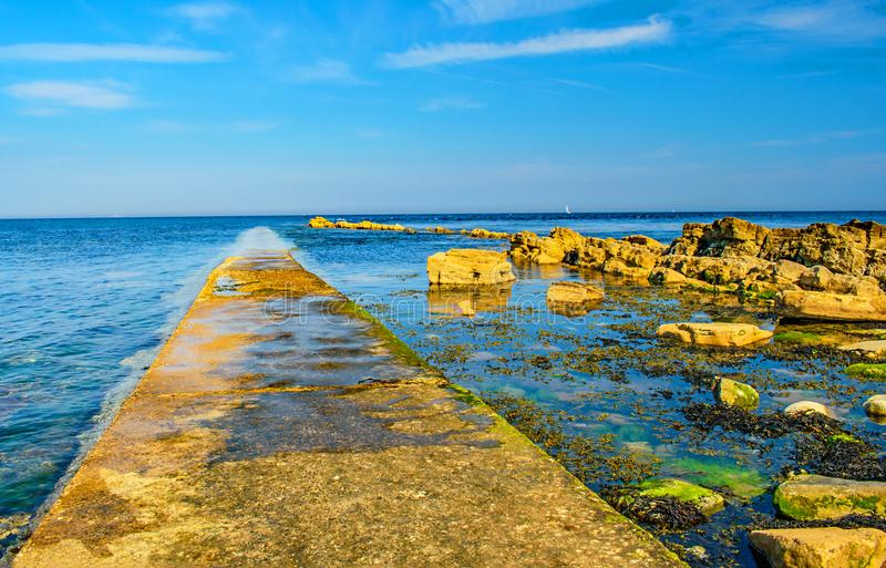 A walkway into the sea,Swanage,Dorset. A view out to sea along the submerging path at Peveril Point,Swanage,Dorset stock photo