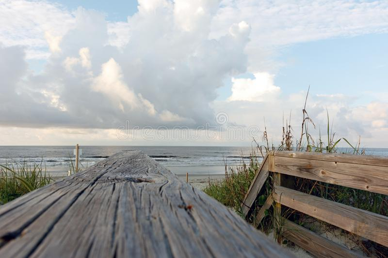 Walkway to the beach with clouds and ocean. Wooden boardwalk path through the sand dunes to the Atlantic Ocean beach, Sunset Beach, North Carolina stock photo