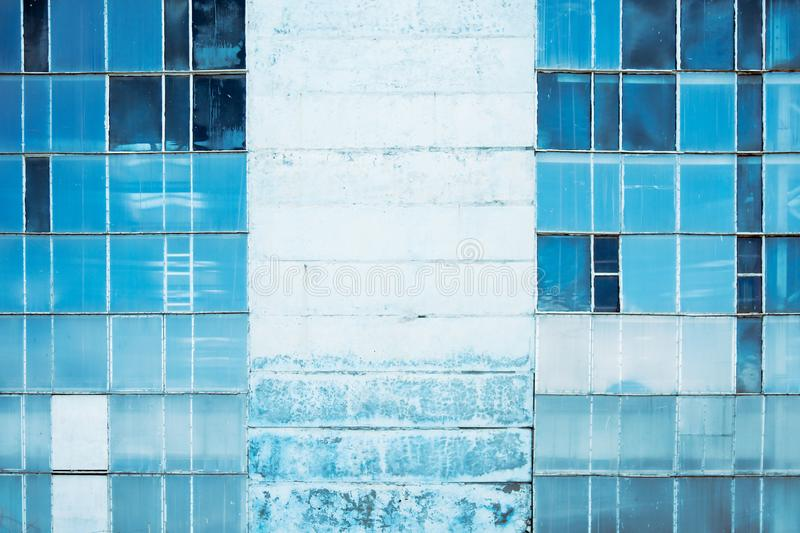 Wall of an abandoned building with stained-glass windows . Blue background . Toned royalty free stock image