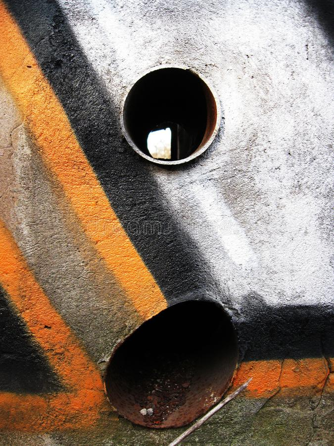 Wall with abstract graffiti in brown and white colors, with orange and black stripes and two holes filled with pipes. royalty free stock image