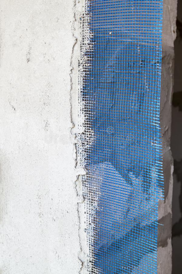 Wall with applied plaster and blue reinforcing grid sticking out from under it. Industrial, plastic, object, block, line, concrete, rough, glue, industry stock image