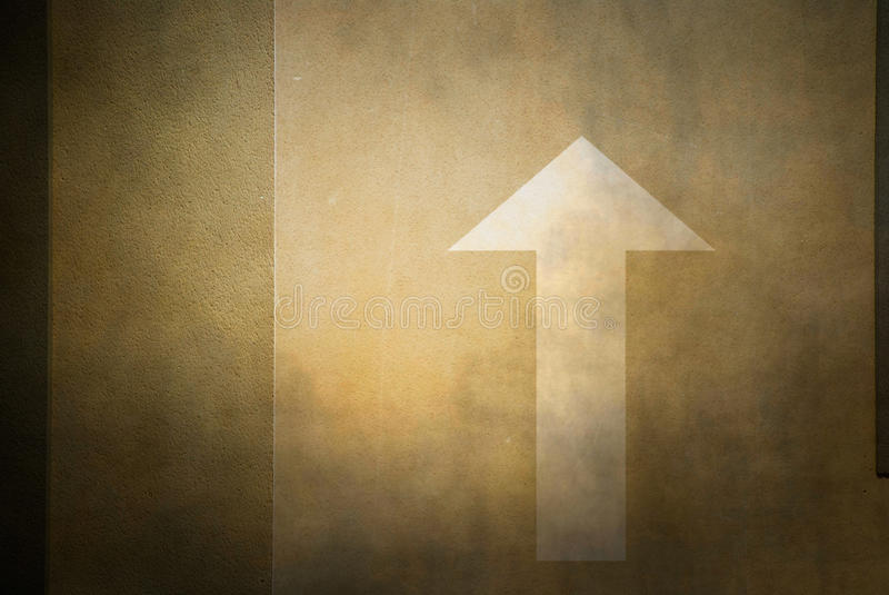 Wall with arrow. Brown wall with white arrow painted on it pointing up royalty free stock images