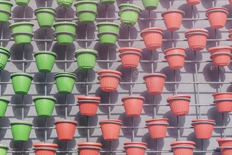 Wall art decor from grid with green and red flower pots on concrete wall. Modern city background, texture. Wall art decor from grid with green and red flower royalty free stock images