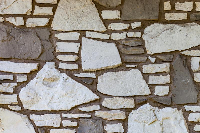 Wall background with irregular sized white and brown stones royalty free stock photography