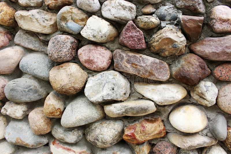 Wall background of large multi-colored stones stock images