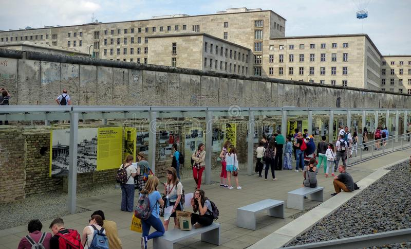 Wall of Berlin with exposing photos and people around in the documentation center, Germany. Travel destination. Blue sky with white clouds. Sunny day. Symbol royalty free stock image