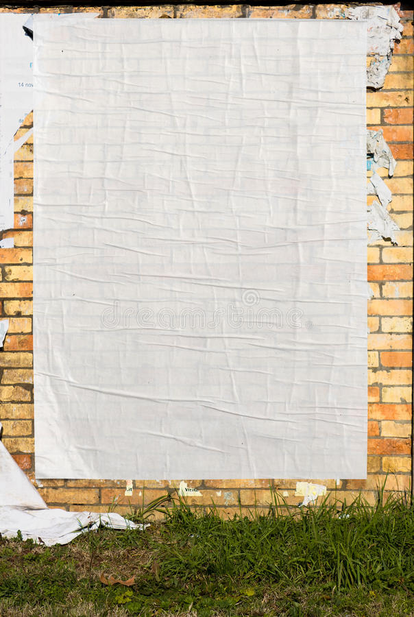 Wall with blank poster. Brick wall with blank poster and torn posters royalty free stock images