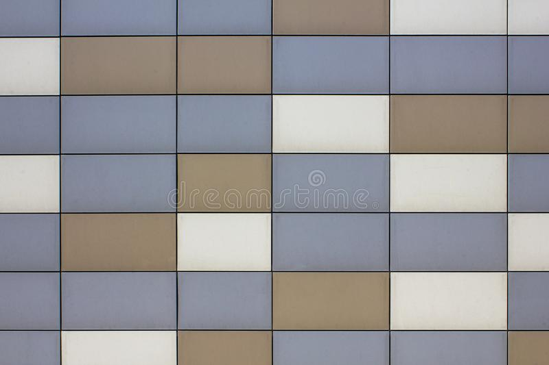 Wall with blue gray brown beige metal rectangular tiles. vertical and horizontal lines. smooth surface texture stock photography