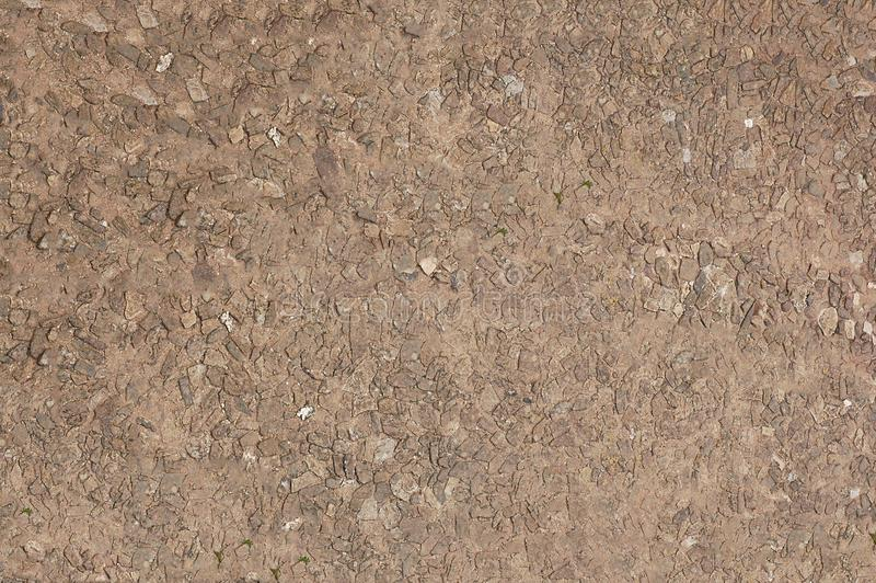 The wall of brown color is made of small stone .Texture or background. royalty free stock photos