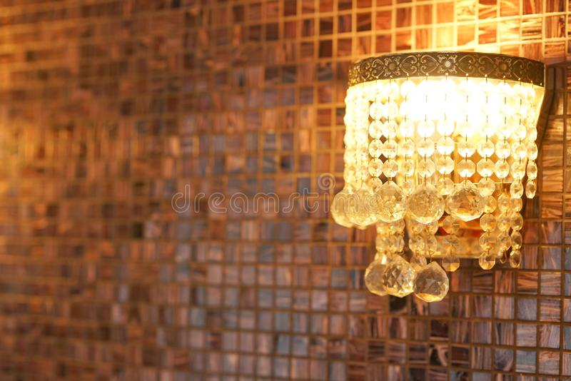 Wall with brown tile with a wood pattern and a crystal chandelier. Nobody stock photography