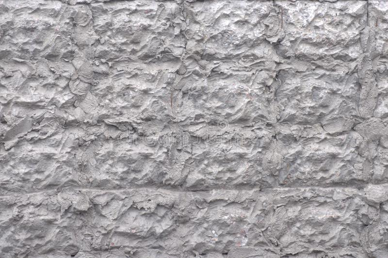 The wall of the building is decorated with a decor of cement. A close-up shot on the street royalty free stock photo