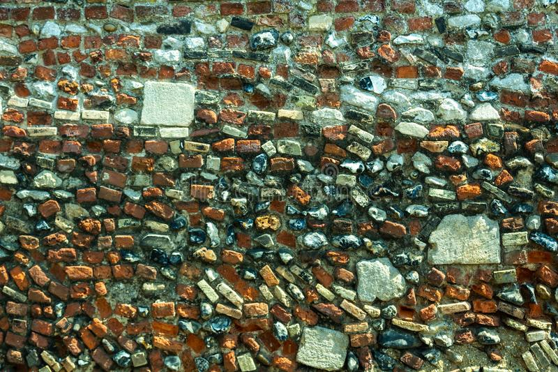 A wall built of different stones and bricks stock photos