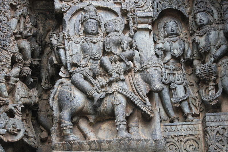 Hoysaleswara Temple Wall Carving of lord shiva and parvati on their bull nandi who has sad face stock image