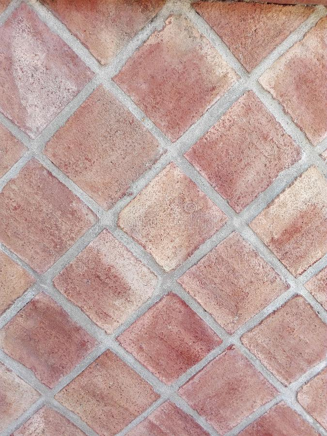 Wall formed by clay tiles. Wall of clay tiles forming rhombuses of brown color royalty free stock photography