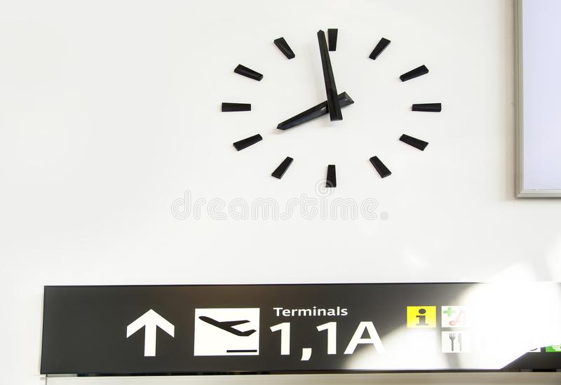 Wall clock at an airport with navigation panel royalty free stock images