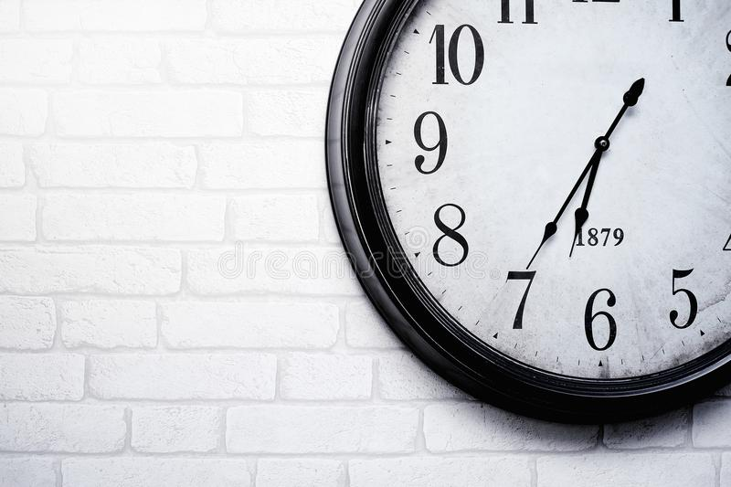 The wall clock is hung on a white brick wall, telling the time accurately. The wall clock vintage is hung on a white brick wall, telling the time accurately royalty free stock photography