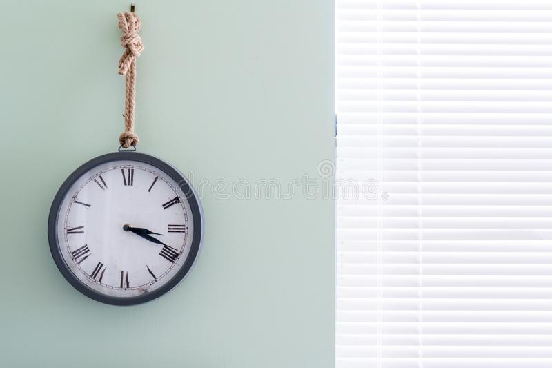 Wall clock with rustic design in a home office, in analog form, pointing to 3 in the afternoon using roman numerals. Wall clock with nautical, rustic design in a royalty free stock images