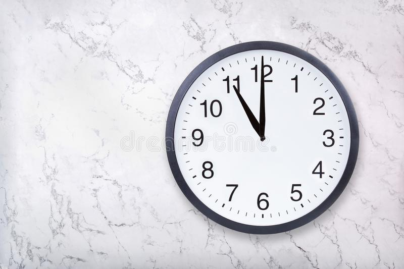 Wall clock show eleven o`clock on white marble texture. Office clock show 11pm or 11am royalty free stock image