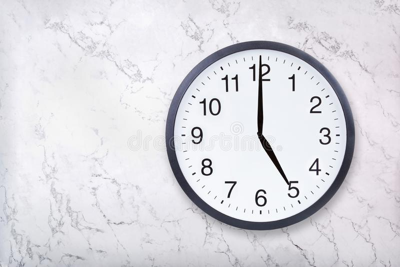Wall clock show five o`clock on white marble texture. Office clock show 5pm or 5am royalty free stock photos