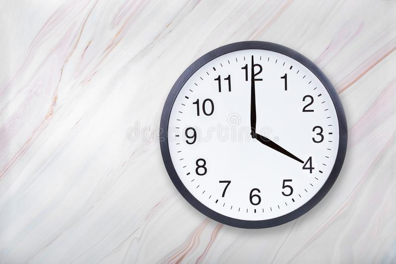 Wall clock show four o`clock on marble texture. Office clock show 4pm or 4am stock photography