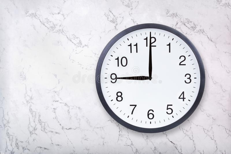 Wall clock show nine o`clock on white marble texture. Office clock show 9pm or 9am royalty free stock photography