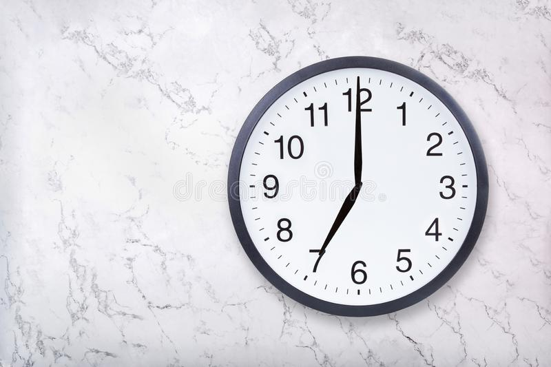 Wall clock show seven o`clock on white marble texture. Office clock show 7pm or 7am royalty free stock photos