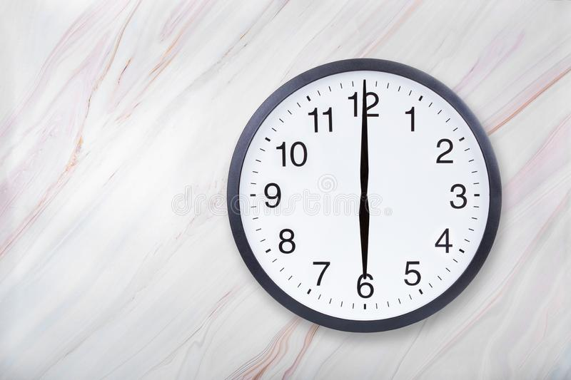 Wall clock show six o`clock on marble texture. Office clock show 6pm or 6am royalty free stock image